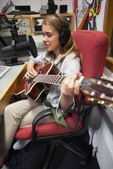 Концентрирование красивой певицы, записывающей и играющей на гитаре