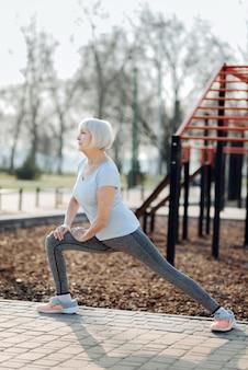 濃度。スポーツ服を着て野外で運動する集中高齢女性