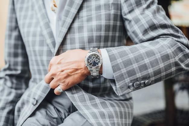 高価な時計を備えたスタイリッシュなグレーのスーツに集中