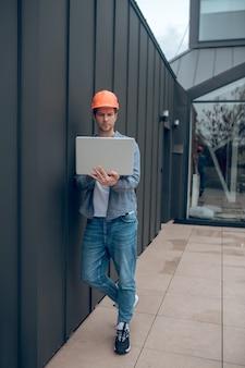 집중. 오후에 새 건물 안뜰 울타리 근처에 서 있는 노트북 작업을 하는 보호용 헬멧을 쓴 진지한 청년