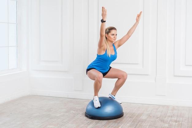 검은 반바지를 입은 스포티한 젊은 운동 금발 여성, bosu 균형 트레이너에서 운동을 하는 체육관에서 일하는 파란색 탑, 피트니스 공에 쪼그리고 앉고, 팔을 들고 균형을 잡고