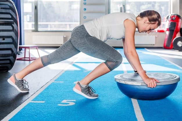 Концентрация спортивная красивая молодая атлетичная блондинка в серых леггинсах, работающая в тренажерном зале, делает планку для мышц живота на тренере баланса босу, держащем баланс на фитнес-клубе