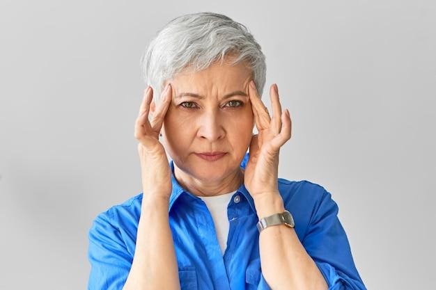 集中力、考え、アイデアの概念。何かを思い出そうとして、寺院に手をつないで、創造的な経験豊富な成熟した実業家。頭痛に苦しんでいる年配の女性、痛みを伴う表情