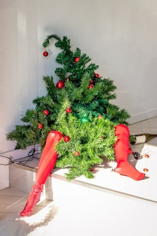 Concept after the holidays tired drunk green christmas tree in red tights