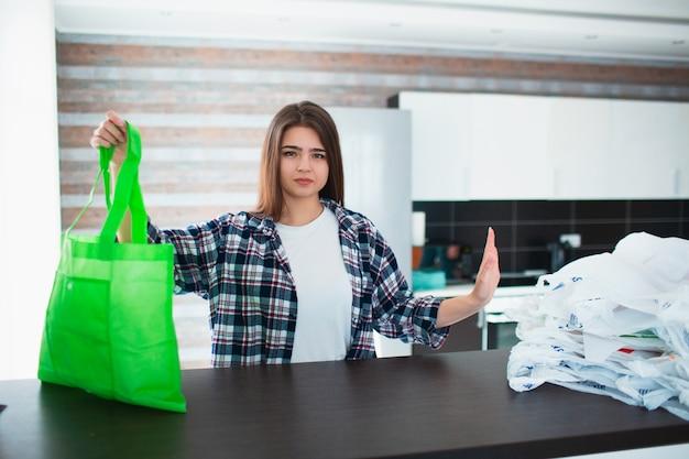 비닐 봉투의 부당한 사용에 대한 개념. 재사용 가능한 백을 사용하여 미세 플라스틱의 자연을 보존하십시오.
