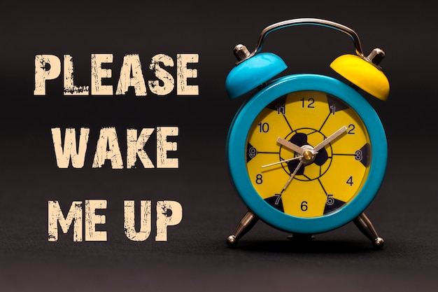 Concept,alarm clock with please wake me up phrase written on black background.