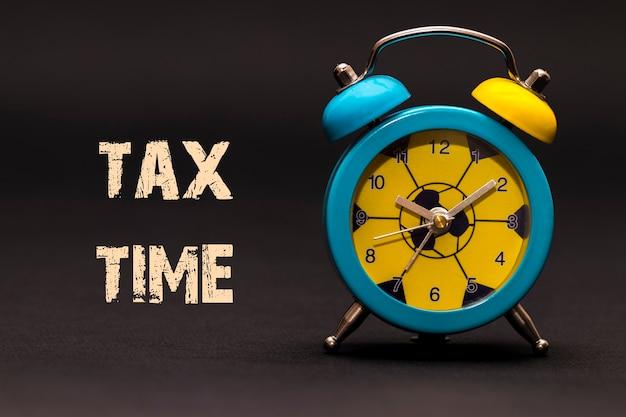 コンセプト、黒の背景に書かれた税の時間のフレーズと目覚まし時計。
