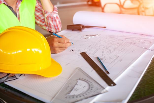 Архитекторы концепции, ручка удерживания инженера указывая архитекторы оборудования на столе с светокопией в офисе, год сбора винограда, свет захода солнца. селективный фокус.