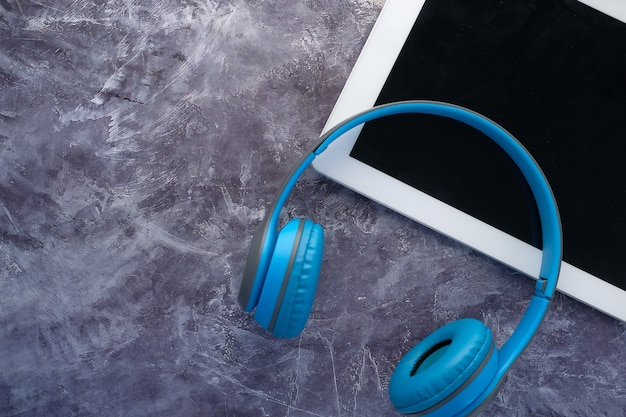 The concept of audio book , headphones and digital tablet on black background