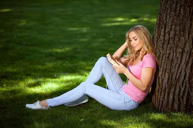 Концептуальная аудиокнига. девушка с книгой и наушниками сидит в парке под деревом.