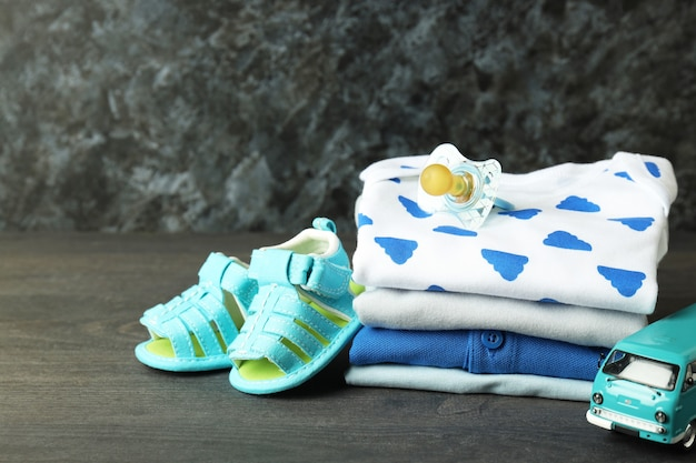 Concept of baby clothes on dark textured table.
