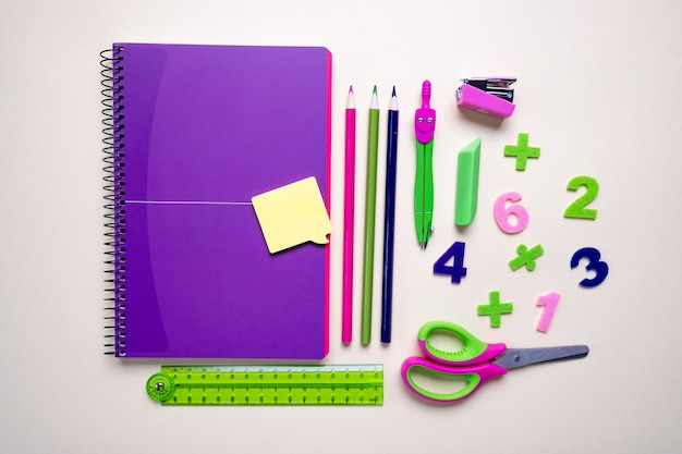Concept back to school. alarm clock and school supplies. top view flat lay