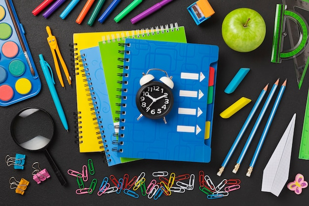 Concept back to school on schedule. alarm clock, notebooks, pencils, student or student tools.