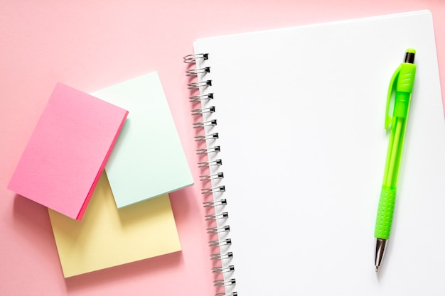 Concept back to school. three multi-colored stickers on a delicate pink background, a white notebook with a spiral and a green pen to sirchu. layout and flat lay with place for text