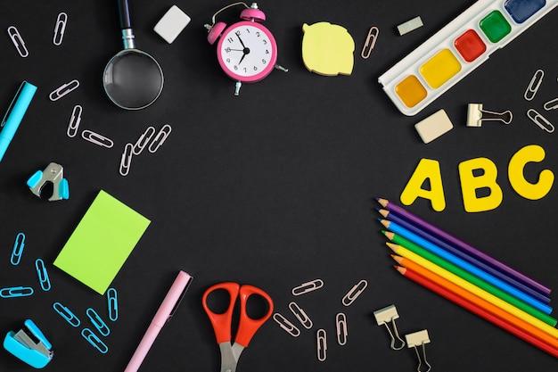 다시 학교로 개념입니다. 검정색 배경에 위에서 사진 멀티 학교 및 사무 용품 거짓말. 텍스트 또는 비문을위한 빈 공간의 중앙에.