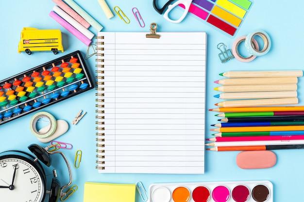 파란색 배경 디자인에 학교 알람 시계 색 분필 연필 노트북 문구로 다시 개념
