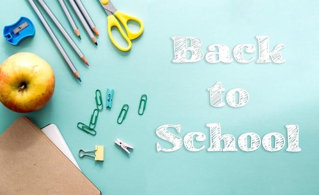 Концепция снова в школу творческий вид сверху. бумага, белые буквы мелом. школьные и офисные принадлежности на светло-синем бумажном фоне. скопируйте пространство, шаблон для текста или дизайна.