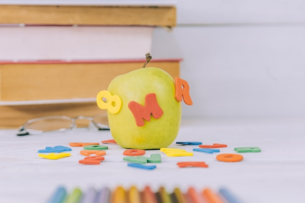 コンセプト学校に戻る。本のスペースに色付きの文字が付いた青リンゴ。