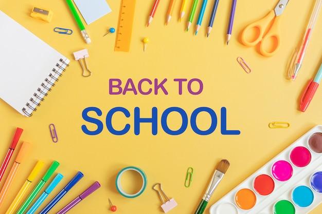 Концепция обратно в школу. школьные канцтовары плоской планировки: акварель, блокнот, ручки, карандаши, точилка, ножницы, линейка, скрепки