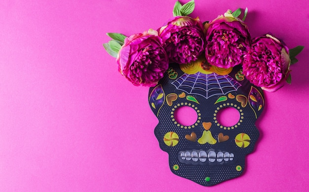 The concept of the background of the holiday dia de muertos. black festive mask skull with flowers on a fuchsia background.