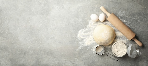 Concept for baking with dough on gray background