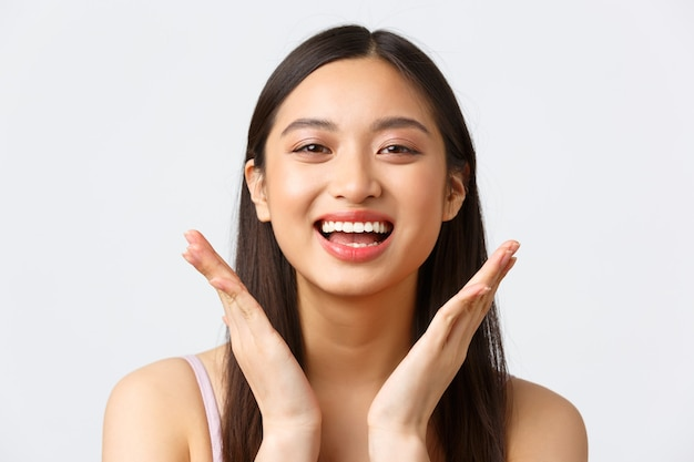 Concept of beauty, fashion and makeup products advertisement. close-up of beautiful asian girl showing her skincare products on face