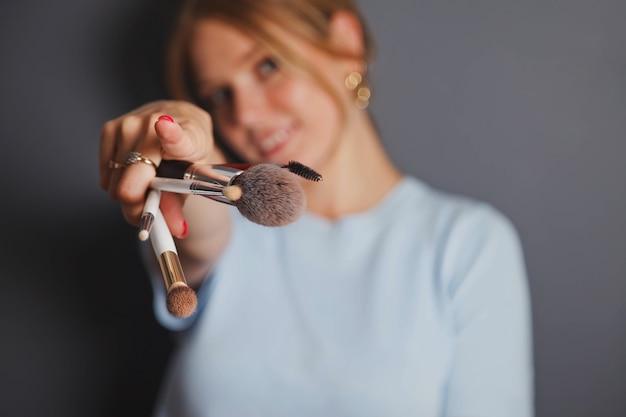 Салон красоты концепции и роскошный макияж. портрет молодой блондинки красоты с кистями для макияжа