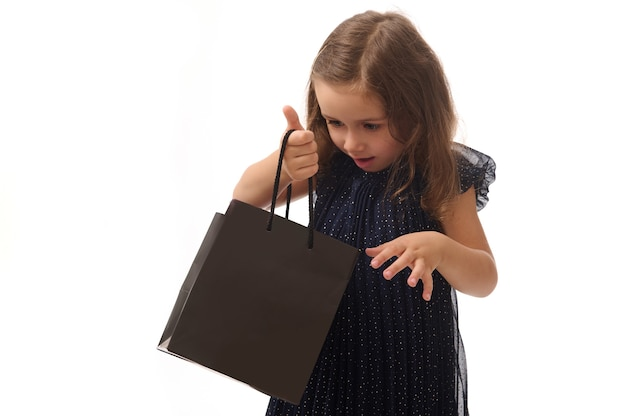 Concept for black friday, isolated portrait of a baby girl in dark blue evening dress with black packet, copy space. shopping, sales and purchases concept