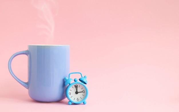 お茶、青いカップ、目覚まし時計のコンセプトブレーク