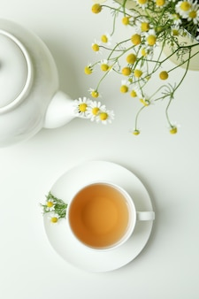 Concept of breakfast with chamomile tea on white table