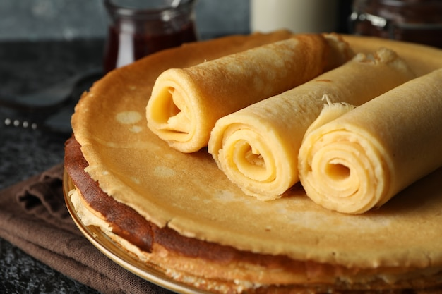 Concept of breakfast with crepes rolls on black smokey table