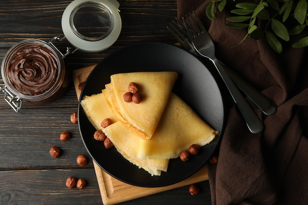 Concept of breakfast with crepes with chocolate paste and nuts on wooden table