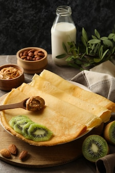 Concept of breakfast with crepes with kiwi, peanut butter and nuts on gray background Premium Photo
