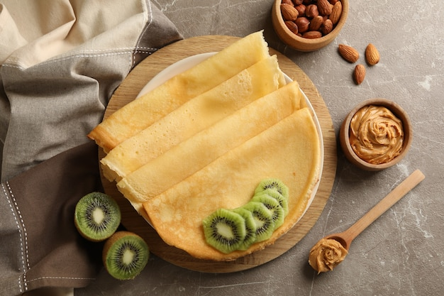 Concept of breakfast with crepes with kiwi, peanut butter and nuts on gray background