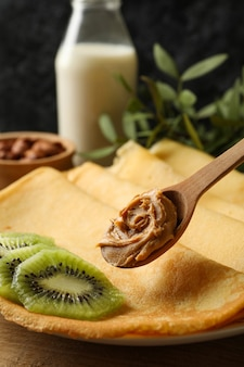 Concept of breakfast with crepes with kiwi and spoon with peanut butter