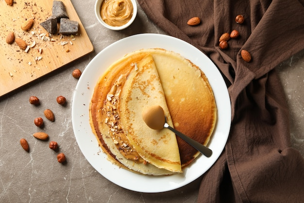 Concept of breakfast with crepes with peanut butter and nuts on gray table