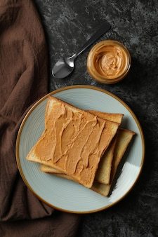 Concept of breakfast with peanut butter toast on black smokey table