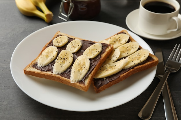 Concept of breakfast with toast with banana on wooden background