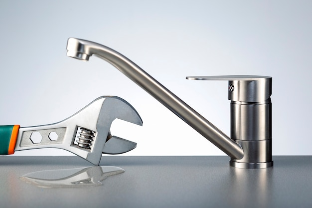 Concept broken plumbing system. faucet, leak water and wrench on dark title surface.