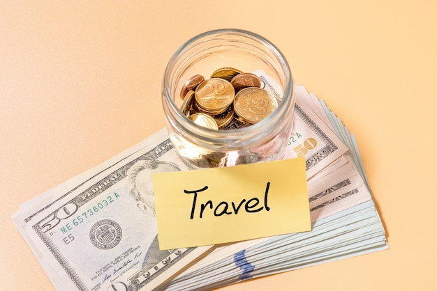 The concept of budget travel. travel savings in a glass jar with coins and a 50 dollar bill