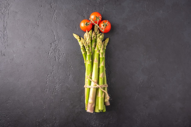 Concept of a bunch of asparagus and cherry tomatoes in the form of a flower