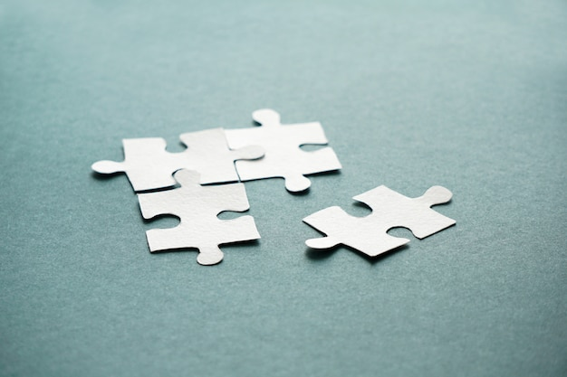 Concept of business, women hands holding  white puzzle pieces on the blue backgroud