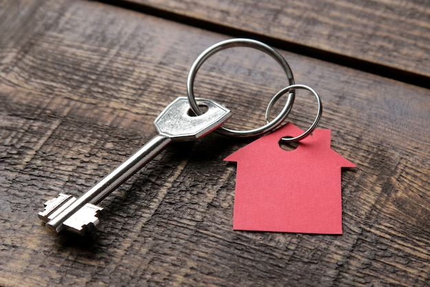Concept of buying a home. keys with keychain house on a brown wooden background close-up.
