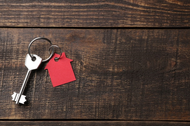 Concept of buying a home. keys with keychain house on a brown wooden background. view from above. with space for inscription