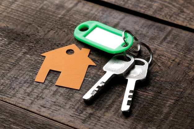 Concept of buying a home. keys with a keychain and a house on a brown wooden background.