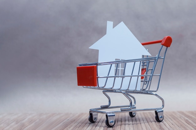 The concept of buying and selling a home. house with paper in the trolley.