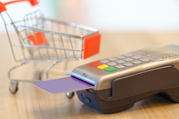 Concept of buying something by money with red shopping cart and magnetic card.