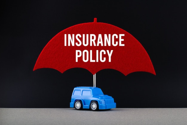 Concept of car insurance. blue car under red umbrella with text insurance policy.