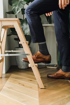 The concept of career growth man's feet go up the stairs