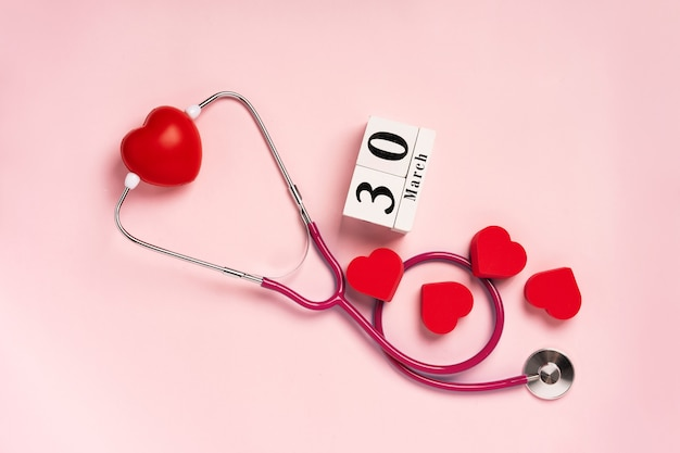 The concept of celebrating doctors day with a stethoscope and a heart on a pink background